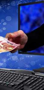 Hand uit computer krijgt geld -uitsnede